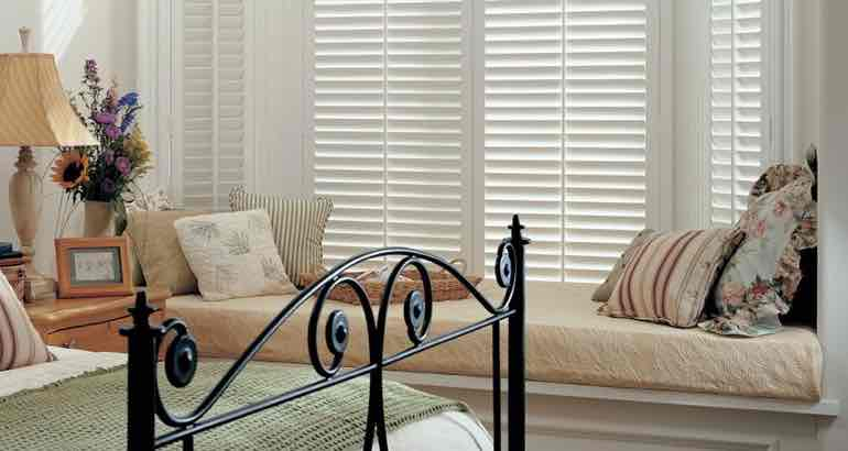 Plantation shutters in a white bedroom bay window.