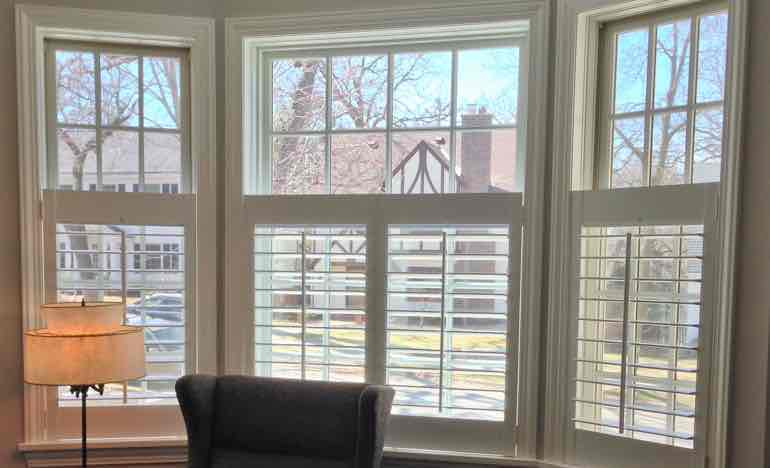 Bottom half white shutters in living room bay window.