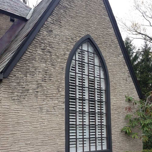 Exterior view of brick home with plantation shutters