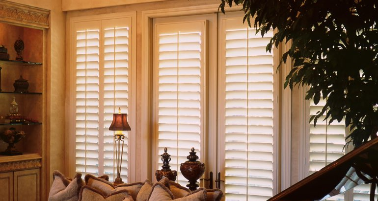 Plantation shutters on french door and window in San Jose parlor