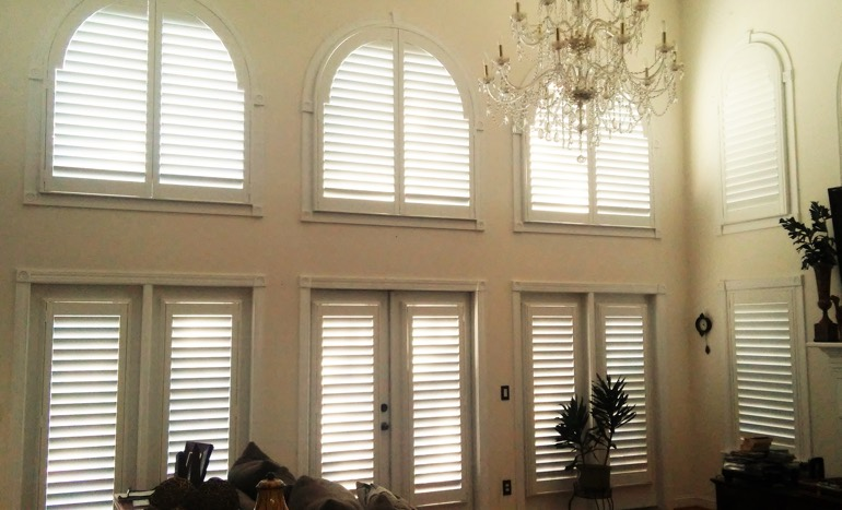 Great room in two-story San Jose home with plantation shutters on high windows.