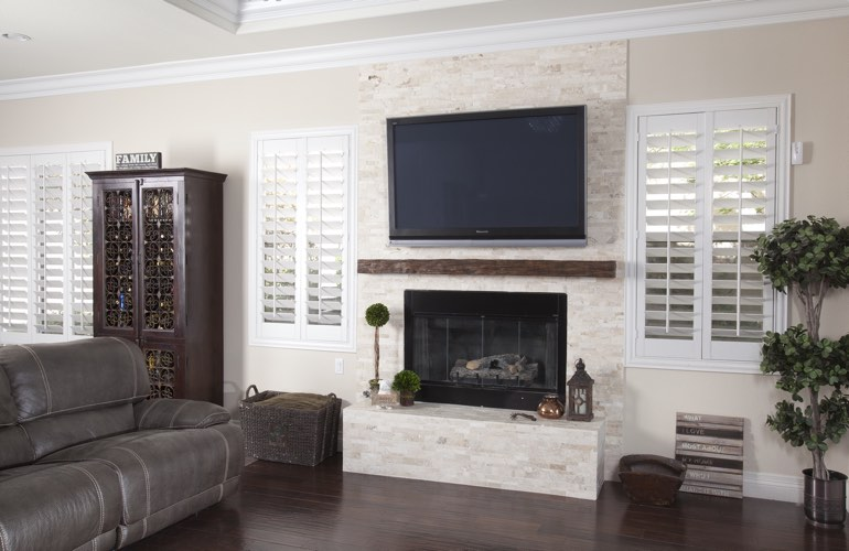 White plantation shutters in a San Jose living room with plank hardwood floors.