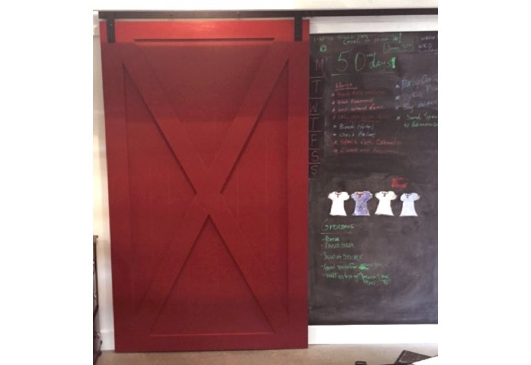 Red x-frame barn door with black track next to chalkboard 🚪