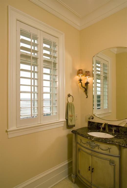 White shutters in a light bathroom give a view of the ocean