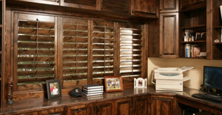 Dark wood shutters in home office.