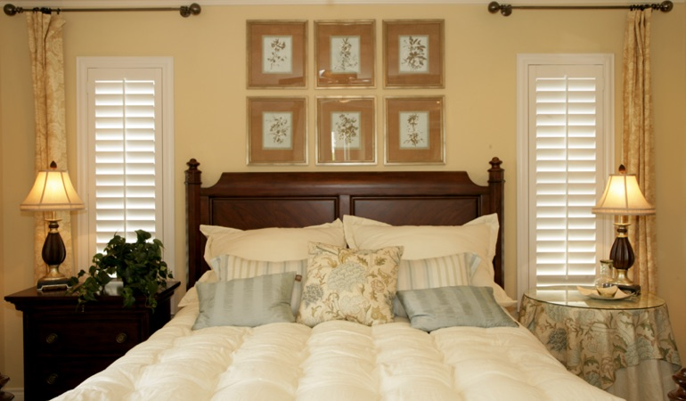 Beige bedroom with white plantation shutters covering windows in San Jose