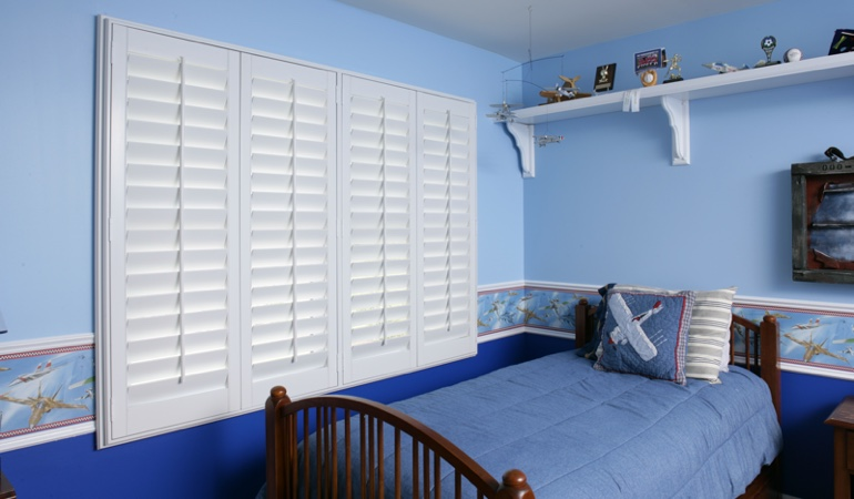 Large plantation shutters covering window in blue kids bedroom in San Jose