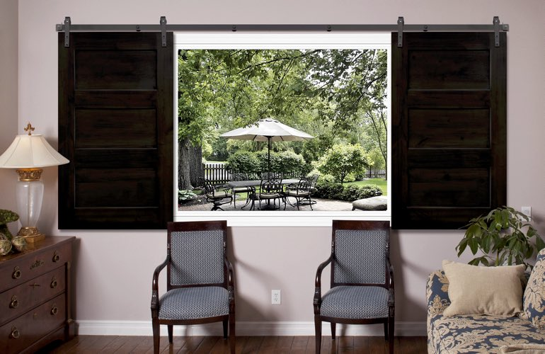 Sliding barn door shutters framing view of patio